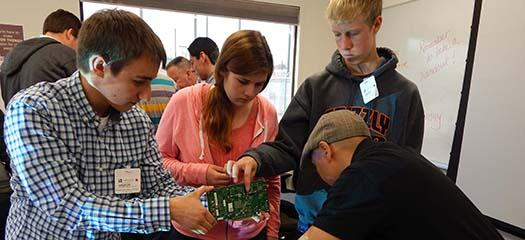 mentors and students inspect a computer motherboard
