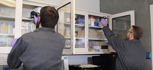 two people conduct RFI scanning in a supply cabinet