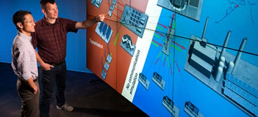 two scientists stand next to a large wall onto which a power grid diagram is projected
