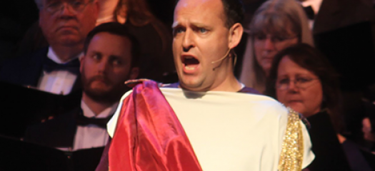 Jarom Nelson performing in Roman dress in front of a choir of formally dressed singers