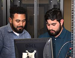 two students confer at a computer workstation