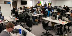 wide shot of the room with hackathon teams working at tables